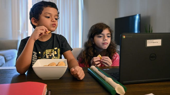Twins Pedro and Luiza Romeiro, third-graders at the Potter Road School in Framingham, take a snack break during a morning of remote learning Wednesday in their Framingham home.
