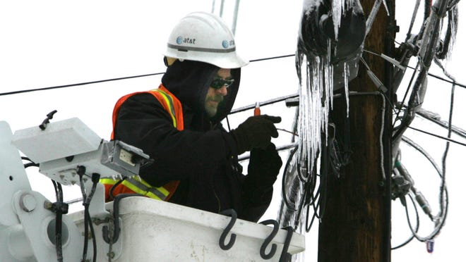 An AT&T worker repaired the telephone lines inLouisville after an ice storm.