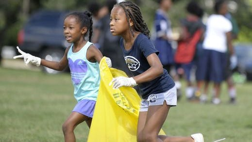 Two years ago, NW Detroit Cougars C-Team Cheerleaders Kaitlyn Henry, left, 8, of Farmington Hills, and Autumn Gilmore, 7, of Warren, pick up trash during Arise Detroit! Neighborhoods Day. (Todd McInTurf, Detroit News, file)