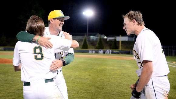 Reynolds' head coach Bryan Craig celebrates with Jimmy Baumstark, left, and Talon James after defeating Roberson and becoming conference champions May 1, 2018.