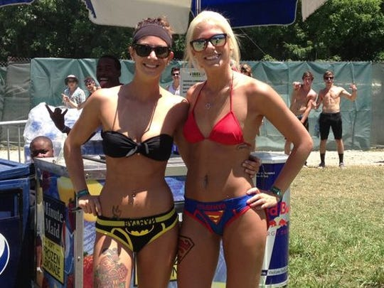 Batgirl and Supergirl seem to relish the attention at Firefly Music Festival.
