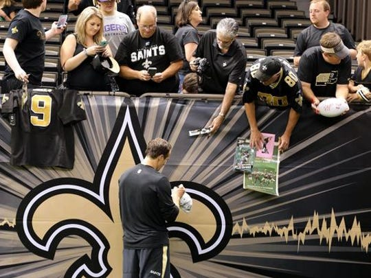 New Orleans Saints quarterback Drew Brees (9) autographs items for fans before their game against the Baltimore Ravens at the Mercedes-Benz Superdome.
