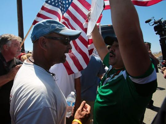 Pro-immigrant supporter Lupillo Rivera (right) and Chris Clinkscales of Murrieta, Calif., get into a shouting match at the Border Patrol station in Murrieta.