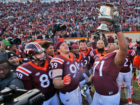 Virginia Tech offensive lineman Jonathan McLaughlin (71) celebrates with Commonwealth Cup as defensive lineman Vinny Mihota (99) joins in after their 52-10 win over Virginia.