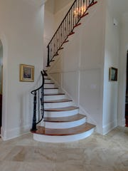 A gorgeous staircase graces the entrance of the home.