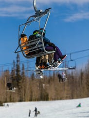 A group of people ride a chairlift to the top of Brian