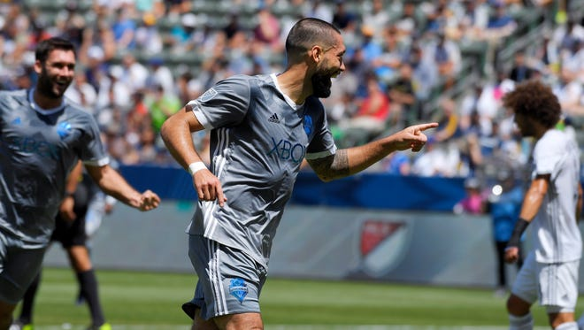 Sounders forward Clint Dempsey (center) celebrates his first-half goal Sunday against Los Angeles.