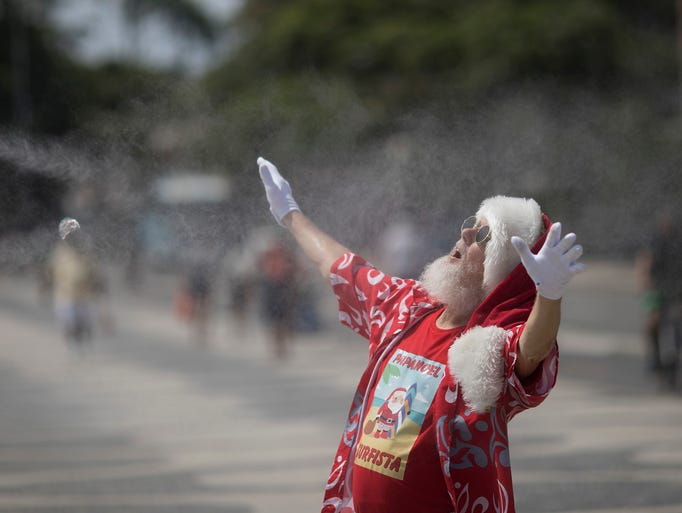Paulo Mourao, 67, cools off as he performs as Santa