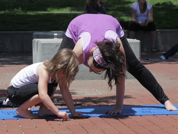 Heather Cobb participates in Yoga on the Square while her daughter, Avery, 6, plays next to her mat at Park Central Square on Friday, June 13, 2014.