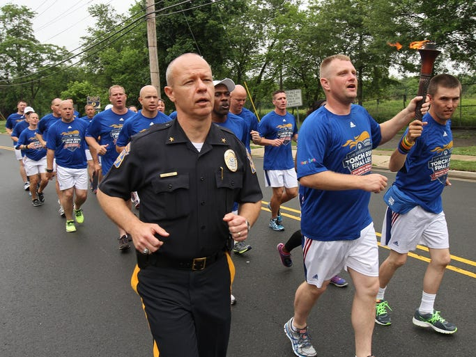 Middlesex Police Chief Scott Young joins in briefly as torch run leaves headquarters. Holding the torch are Jared Shepard, Police Officer from Nebraska, center, and Lewis Fancher, Special Olympic Athlete from Wyoming. A torch run to kick off the Special Olympics USA games stops by the Middlesex Borough Police Department for a brief ceremony, June 13, 2014. Middlesex NJ. photo by Kathy Johnson  BRI EST 0614 Torch Run for Special Olympics USA games