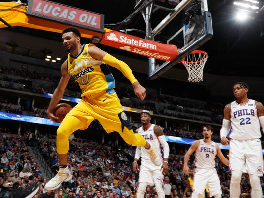 Denver Nuggets guard Jamal Murray, left, flies out of bounds while trying to save a loose ball as, from back left, Philadelphia 76ers forwards Robert Covington, Dario Saric, of Croatia, and Richaun Holmes look on in the first half of an NBA basketball game Saturday, Dec. 30, 2017, in Denver. (AP Photo/David Zalubowski)