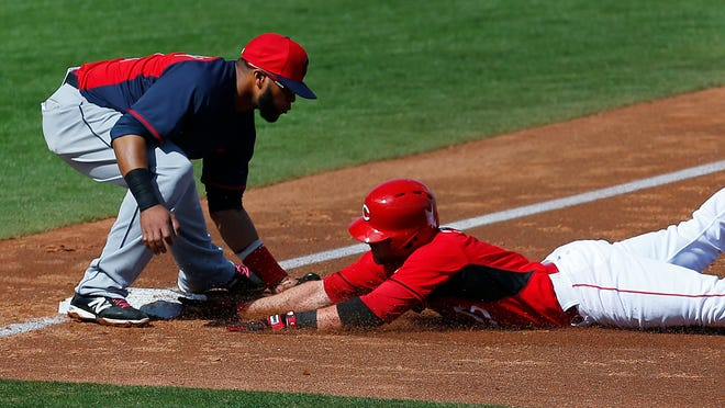 The only time Carlos Santana, left, touched the ball in the field at third was to tag out Zack Cozart here during the second inning.