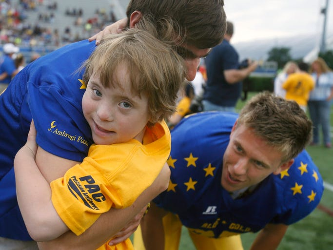 Aaron Janusz hugs his hand-in-hand companions Brandon Goodge and Tyler Taschner of Tatnall before the DFRC Blue-Gold All-Star Football game, Saturday, June 21, 2014 at Delaware Stadium.
