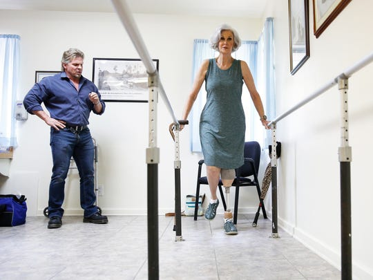 Theresa Neubauer takes first steps with her new prosthetic leg as Jeff Fredrick of Rehab Engineering observes her movements.