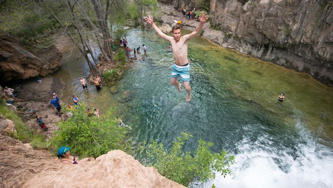 Josh Gillick jumps off the waterfall at Fossil Creek on Saturday, June 13, 2015.