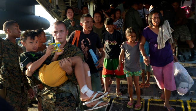 A U.S. Marine carries an injured boy off a military cargo plane that flew Typhoon Haiyan survivors out of Tacloban to Manila on Tuesday.
