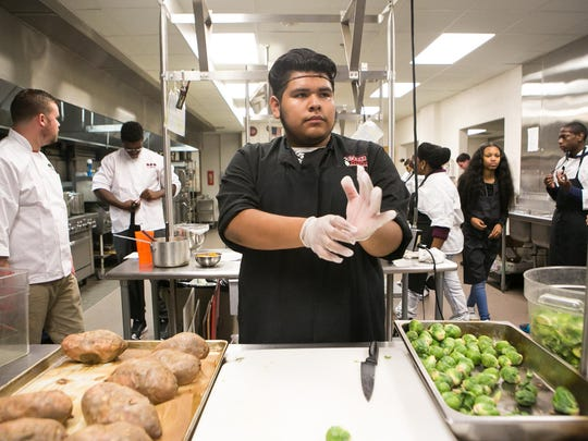 William Penn High student Andrew Avilez puts gloves on as he gets ready to prep food.