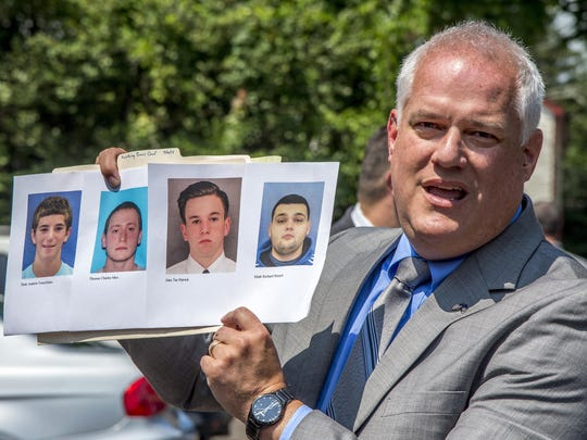 Bucks County District Attorney Matthew Weintraub holds up photos of four men who are missing during a news conference in Solebury Township, Pa., Monday, July 10, 2017. The four men, who went missing last week, are Dean Finocchiaro, from left, Tom Meo, Jimi Tar Patrick and Mark Sturgis.