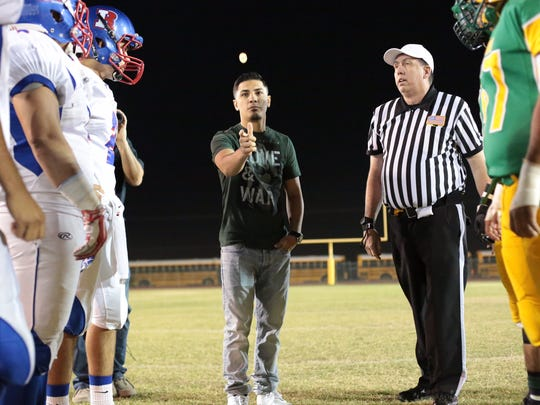 Boxer Randy Caballero tosses the coin for the Indio vs. Coachella Valley rivalry game on Friday.