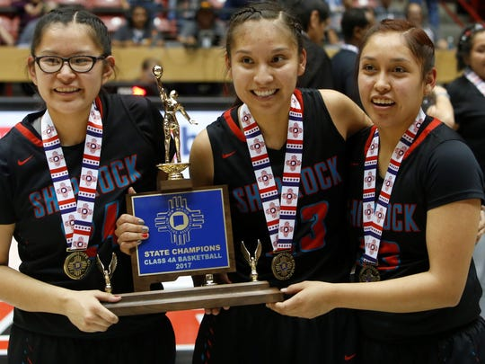 From left, Shiprock seniors Tierra Clichee, Tanisha Begay and Kacy Begay pose with the 4A state championship trophy on Friday at The Pit in Albuquerque.