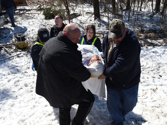Emergency personnel carry Arthur Greathouse, of Sycamore Springs Road, to a waiting ambulance on Friday.