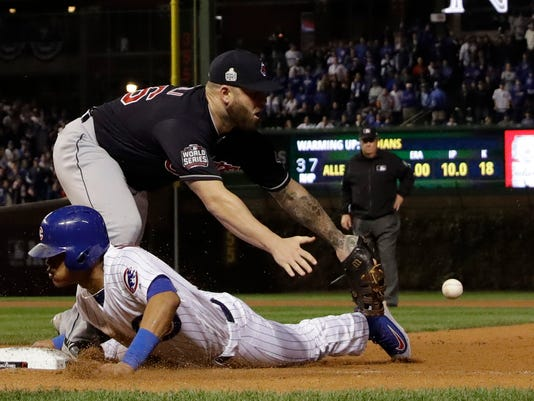 Chicago Cubs' Addison Russell slides back to first as Cleveland Indians' Mike Napoli has trouble with the throw on a pick off attempt during the ninth inning of Game 4 of the Major League Baseball World Series Saturday, Oct. 29, 2016, in Chicago. (AP Photo/David J. Phillip)
