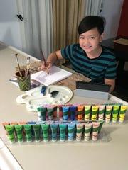 Liam Padua, 10, at work. Padua has been creating artwork