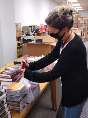 """Tanya Jones of the Gaston County Public Library prepares bundles for sale in the library's """"virtual"""" book sale."""