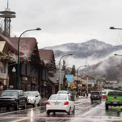 Rain falls as cars drive through downtown Gatlinburg,