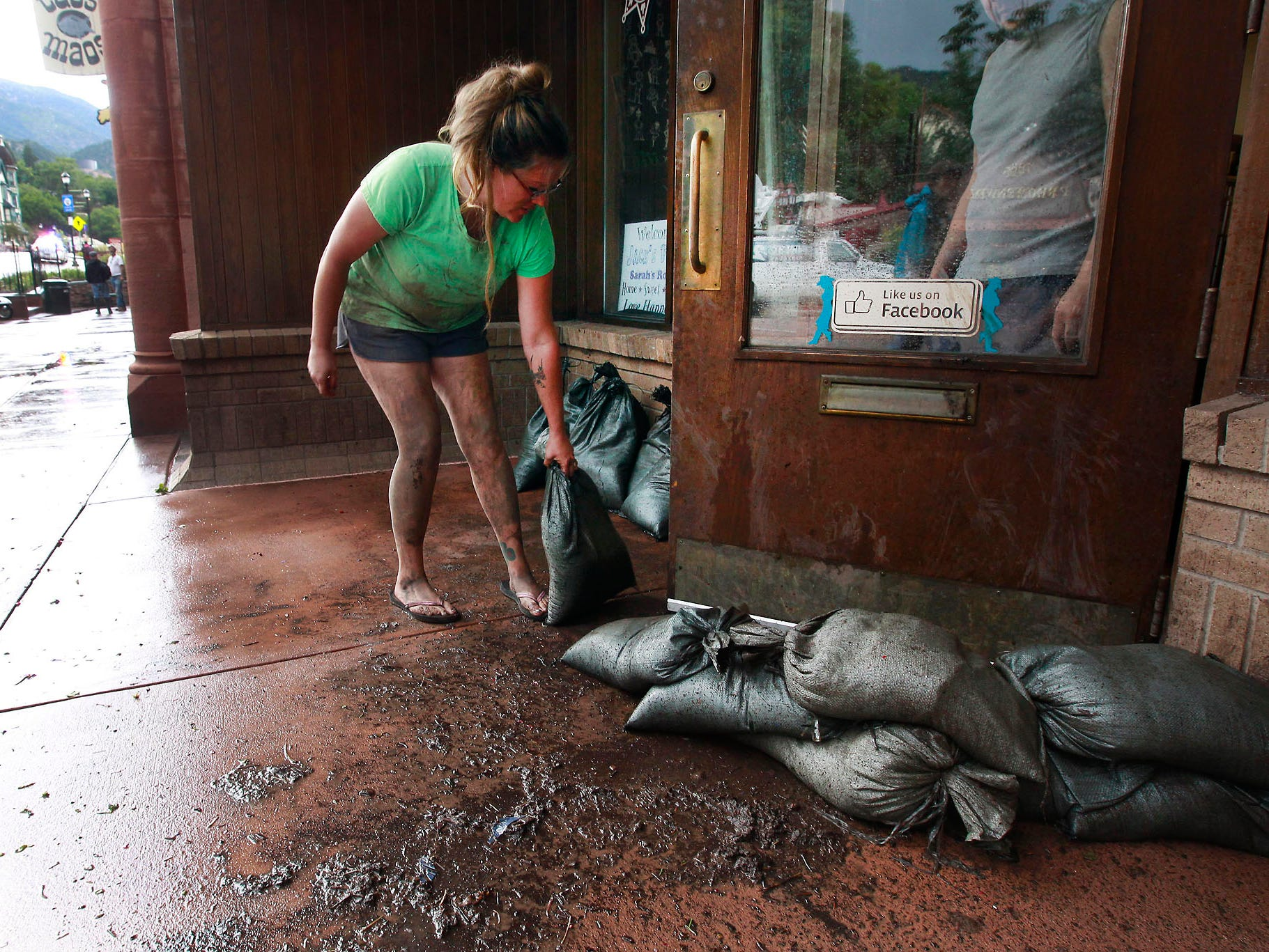 Angie Findley arranges sand bags in front of her heavily damaged store.