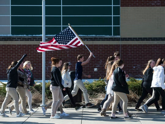 A student runs through the crowd with an American flag