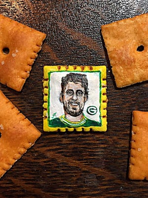 Inspired by Aaron Rodgers' brilliant performance against the Dallas Cowboys, artist John Kettman painted the Packers quarterback on a Cheez-It cracker. --- Photo by John Kettman