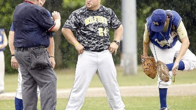 From a 2014 game, Framingham Post 74 manager Bunkie Smith (left) and Milford Post 59 manager Steve DiVitto (center) discuss continuing the game while Framingham's Noah Gilman scrapes the mud from his cleats.