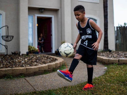 Jaron Couture, 7,  kicks the ball in his front yard