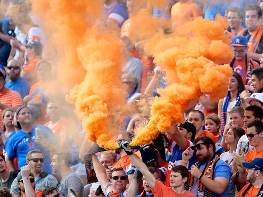 FC Cincinnati fans pop smoke bombs in the Bailey at the start of the first half of the USL soccer match between FC Cincinnati and the Charleston Battery at Nippert Stadium on the University of Cincinnati campus in Cincinnati on Saturday, July 30, 2016. At the half, the match was tied 0-0.