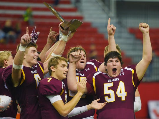 Madison raises the 11A trophy above their heads after the game against Dakota Valley Saturday, Nov. 11, at the DakotaDome in Vermillion.