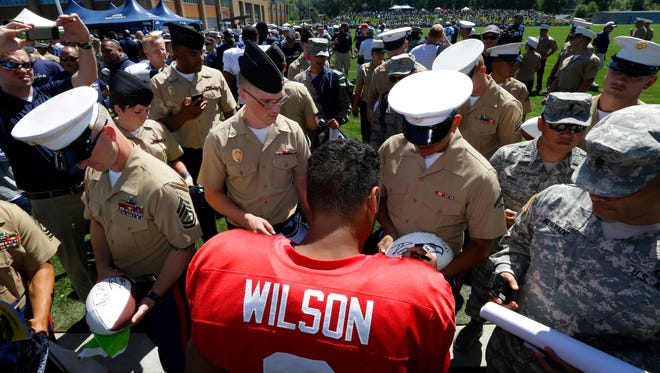 Seattle Seahawks quarterback Russell Wilson signs autographs for U.S. Marines and other military members attending NFL training camp, Thursday, July 31, 2014, in Renton, Wash.