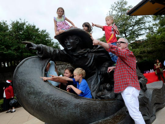 "Author William Joyce poses with children next to the statue in Everman Park based upon a scene in his 1993 book, ""Santa Calls."" Joyce featured Abilene in the book by chance, which subsequently helped launch the Key City's National Center for Children's Illustrated Literature 20 years ago."