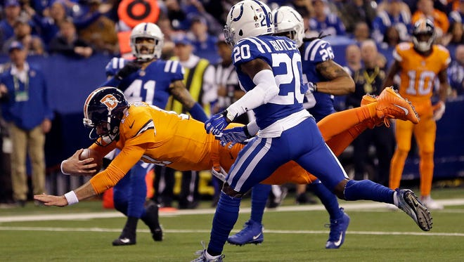 Broncos quarterback Brock Osweiler (17) dives in for a touchdown in front of Colts free safety Darius Butler (20) during the first half on Thursday.