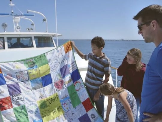 Green Bay Packers quarterback Aaron Rodgers looks over a survivors' quilt with the kids from Camp Hometown Heroes.