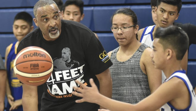 Phil Handy, assistant coach for the Cleveland Cavaliers, sets up a three-man- weave drill at a basketball clinic held at Okkodo High School on Thursday.