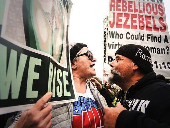 A protestor argues with a woman participating in the
