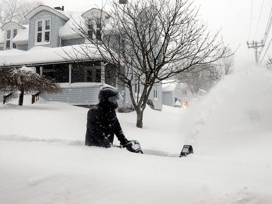 A homeowner wades through waist-deep snow as he snow