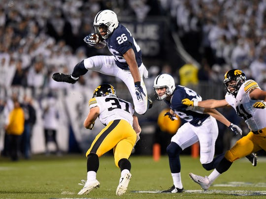 Penn State running back Saquon Barkley leaps over Iowa defensive back Brandon Snyder during their game in 2016.