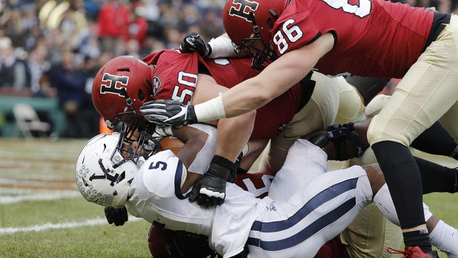 Yale running back Alan Lamar (5) is tackled by Harvard defensive tackle Richie Ryan (50) and defensive end John Pirrmann (86) during the first half at Fenway Park in Boston, Nov. 17, 2018.