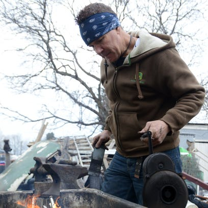 Todd Bitler stokes the fire around a knife he's creating