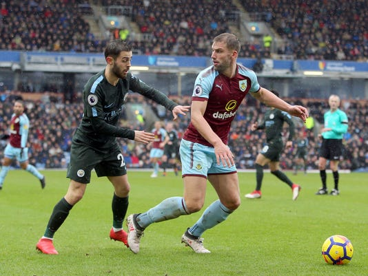 Manchester City's Bernado Silva, left and Burnley's Charlie Taylor battle for the ball, during the English Premier League soccer match between Burnley and Manchester City at Turf Moor, in Burnley, England, Saturday Feb. 3, 2018. (Richard Sellers/PA via AP)