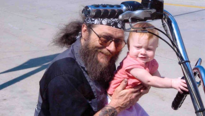 Michael L. Funk of Neenah, shown here holding one of his  granddaughters, was killed in Saturday's hostage standoff in downtown Neenah.