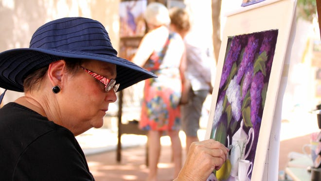 Deming artist Lyn Orona worked on her canvas during an outdoor summer show in the Arts Park back in 2015.