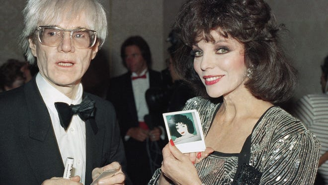Actress Joan Collins chats with Andy Warhol, April 1, 1985. She holds a snapshot of a portrait Warhol painted of her.